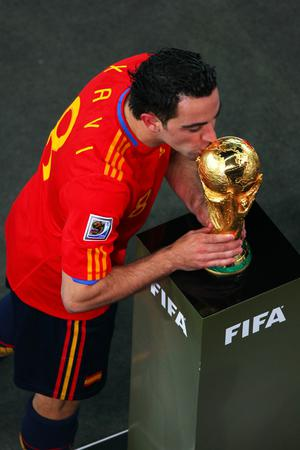 Xavi Hernandez of Spain kisses the World Cup as he collects his medal during the 2010 FIFA World Cup South Africa Final match between Netherlands and Spain at Soccer City Stadium on July 11, 2010 in Johannesburg, South Africa