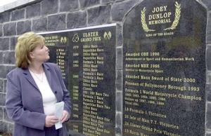 Linda Dunlop, Joey Dunlop's wife, reads the list of Joey's victories that are engraved on the plinth in the Joey Dunlop Memorial garden that was opened in his home town of Ballymoney, Co. Antrim