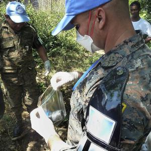 UN investigators take samples behind a Nepalese peacekeeping base in Haiti amid a search for the cause of the cholera outbreak (AP)