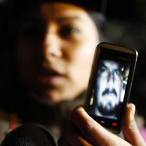 A relative shows on his mobile phone new images of the trapped miners in Copiapo, Chile (AP)