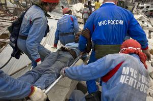 Pierre Louis Ronny is rescued after having spent a week trapped under the Teleco Haitian telecom building downtown January 19, 2010 in Port Au Prince, Haiti.
