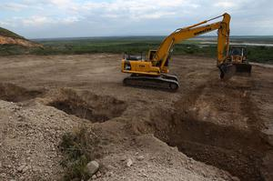 An excavator prepares graves for the bodies of victims of last week's devastating earthquake near the town of Titanyen