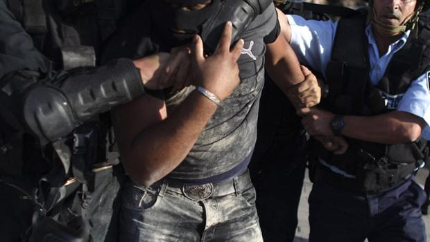 Israeli police detain a masked Arab Israeli protester during clashes in the northern Arab Israeli town of Umm el-Fahm, Monday, May 31, 2010