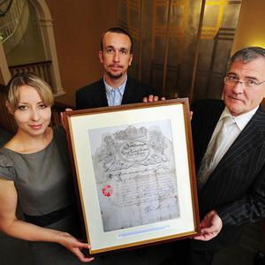 Dr Emma Saunders, Osgar O'Neill, and Enda Connellan hold the ship's pass signed by King James II and Samuel Pepys