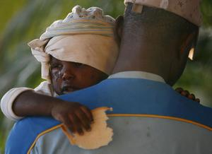 A young injured earthquake survivor holds a piece of bread in a makeshift shelter in Port-au-Prince, Haiti, Thursday, Jan. 14, 2010.