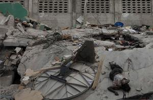 A body lies among the rubble of a damaged building in Port-au-Prince, Wednesday, Jan. 13, 2010.