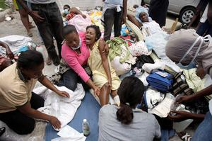A woman is treated for her wounds on the grounds of the Canape-Vert Hospital in Port-au-Prince, Haiti, Thursday, Jan. 14, 2010.
