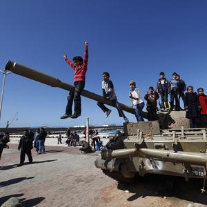 A Libyan boy sits on the barrel of a destroyed army tank as he and other youths celebrate the freedom of the city of Benghazi (AP)