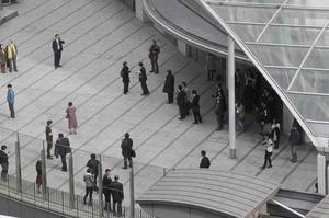 Office workers in Tokyo's Shiodome district near Tokyo Bay stay on the pedestrian deck Friday, March 11, 2011, shortly after a  7.9-magnitude earthquake has struck off Japan's northeastern coast. (AP Photo/Koji Sasahara)