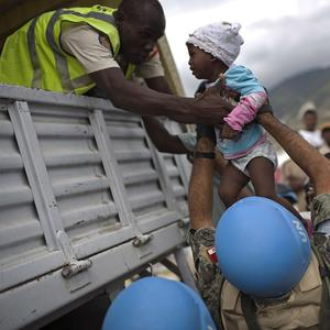 UN soldiers help an aid worker take a little girl up into a truck as earthquake survivors are evacuated in Port-au-Prince, Haiti (AP)