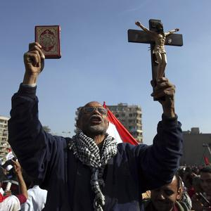 An Egyptian protesters holds a cross and a Koran as he chants anti-Muslim Brotherhood slogans at an opposition rally in Cairo (AP)