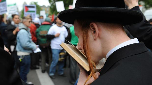 An Hasidic Jew, a group who traditionally do not agree with Israel's action against Palestine, reads scripture during a campaign in Whitehall, London