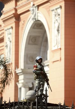 A soldiers stands guard in front of the Egyptian museum in Cairo, Sunday, Jan. 30, 2011. The Arab world's most populous nation appeared to be swiftly moving closer to a point at which it either dissolves into widespread chaos or the military expands its presence and control of the streets. (AP Photo/Ahmed Ali)