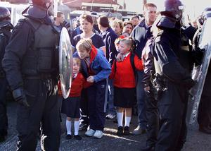 Catholic school children and their parents make their way to Holy Cross school under a heavy police and British Army presence in the Ardoyne area of North Belfast, Northern Ireland, Tuesday, Sept. 4, 2001.  (AP Photo/Peter Morrison)