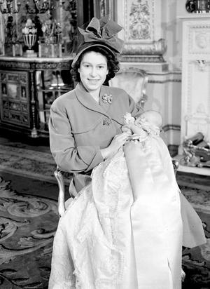 1948:  Princess Elizabeth - later to become Britain's Queen Elizabeth II - holds her son, the Pince of Wales, after his christening ceremony in Buckingham Palace. PA Photo.