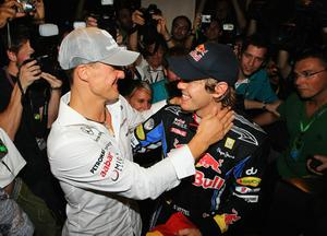 ABU DHABI, UNITED ARAB EMIRATES - NOVEMBER 14:  Race winner and F1 2010 World Champion Sebastian Vettel (R) of Germany and Red Bull Racing is congratulated by Michael Schumacher (L) of Germany and Mercedes GP following the Abu Dhabi Formula One Grand Prix at the Yas Marina Circuit on November 14, 2010 in Abu Dhabi, United Arab Emirates.  (Photo by Paul Gilham/Getty Images)