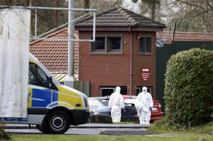 Police Forensic officers examine the scene at the Massereene army barracks in Antrim, west of Belfast, Northern Ireland Sunday, March, 8, 2009 after two British soldiers were shot to death and four other people wounded in a drive-by ambush that politicians blamed on IRA dissidents. Suspected IRA dissidents who opened fire on British soldiers and pizza delivery men outside an army base shot their victims again as they lay wounded on the ground, police said Sunday. Two soldiers died and four other people, including two men delivering pizzas, remained hospitalized with serious wounds following Saturday night's attack at the entrance to Massereene army barracks in Antrim, west of Belfast.  (AP Photo/Peter Morrison)
