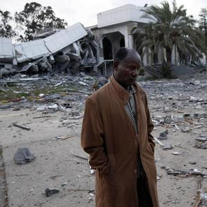 A Libyan official stands next to a destroyed library at Muammar Gaddafi's compound (AP)
