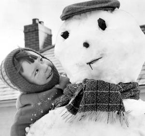 With no worries about outlook of further snow three-year old Kenneth Moore, Greenacres, Ballyutoag, Ligoniel, admires his giant snowman in the garden of his home.   21/1/1965