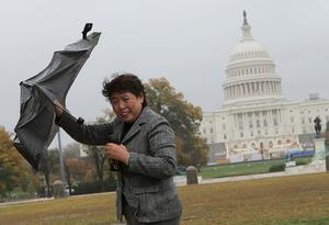 WASHINGTON, DC - OCTOBER 29:  A tourist struggles against gusting winds as the leading edge of Hurricane Sandy moves across the nation's capital on October 29, 2012 in Washington, DC. Hurricane Sandy is expected to make landfall later this evening in southern New Jersey. (Photo by Win McNamee/Getty Images) *** BESTPIX ***