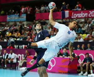 LONDON, ENGLAND - JULY 31:  Daniel Narcisse of France jumps ahead of Gonzalo Matias Carou of Argentina during the Men's Handball Preliminary match between Argentina and France on Day 4 of the London 2012 Olympic Games at The Copper Box on July 31, 2012 in London, England.  (Photo by Jeff Gross/Getty Images)