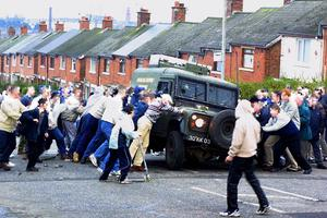 Ardoyne residents try to overturn an army landrover in Ardoyne avenue after trouble flared up again outside the nearby Holycross school. Picture: Pacemaker