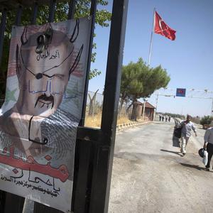 Syrian refugees walk past a defaced poster of president Assad as they head for Turkey (AP)