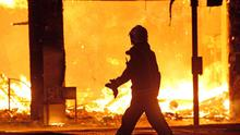 A fire-fighter walks past a burning  property near Reeves Corner, Croydon,  as rioters were rampaging across Britain's capital again