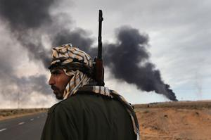 RAS LANUF, LIBYA - MARCH 09:  A Libyan rebel scans the frontline as a facility burns on the frontline on March 9, 2011 near Ras Lanuf, Libya. The rebels pushed back government troops loyal to Libyan leader Muammar Gaddafi towards Ben Jawat.  (Photo by John Moore/Getty Images)