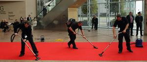 Workmen vacuum the red carpet in the Convention Centre Dublin for an evening of British and Irish music and fashion