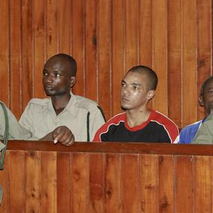 Briton Jermain Jhon Grant is guarded by prison wardens at his trial on terrorism charges in Mombasa (AP)