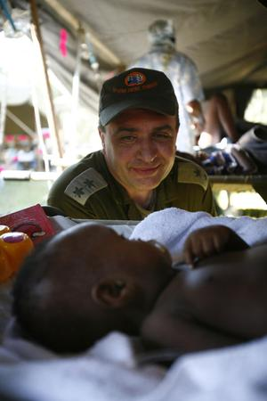 Avi Berman, of Israel, sits next to a baby that was rescued from the collapsed house where his parents died during last week's earthquake at and Israeli Field Hospital in Port-au-Prince, Monday, Jan. 18, 2010. (AP Photo/Ricardo Arduengo)
