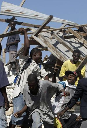 Men fight for goods taken from quake-damaged stores in downtown Port-au-Prince, Haiti, Monday, Jan. 18, 2010. Looting spread to more parts of downtown as hundreds of people clambered up broken walls to break into shops and take whatever they could find.  (AP Photo/Francois Mori)