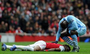 LONDON, ENGLAND - APRIL 08:  Mario Balotelli of Man City apologises to Alex Song of Arsena during the Barclays Premier League match between Arsenal and Manchester City at Emirates Stadium on April 8, 2012 in London, England.  (Photo by Michael Regan/Getty Images)