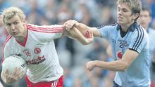 Can't stop me: Tyrone's Owen Mulligan attempts to break free from a Michael Fitzsimons tackle
