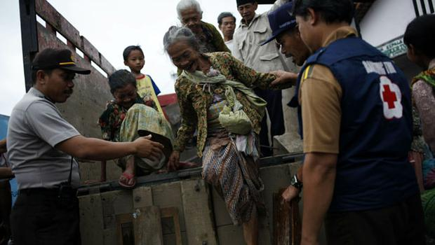 YOGYAKARTA, INDONESIA - OCTOBER 26:  A police officer helps a villager step down from a truck after being evacuated from their village to Girikerto village in Sleman, on October 26, 2010 near Yogyakarta, Indonesia. Authorities will evacuate more than 11,000 villagers living on the slopes of the Mount Merapi volcano near Yogyakarta on Java after the alert status for an eruption was raised to the highest level. (Photo by Ulet Ifansasti/Getty Images)