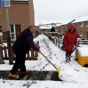 A man clears paths in Auchterarder, Scotland, after six inches of snow fell overnight