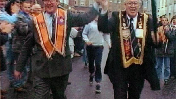 (from video) of UUP leader David Trimble and DUP leader Ian Paisley walk hand in hand in the centre of Portadown celebrating the fact that Orangemen were allowed to walk the Nationalist Garvaghy Road.