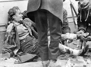 After the blast - injured and shocked, a woman lies helpless on the pavement after the Donegal Street bomb blast, as people rush to give medical assistance.  20/3/1972