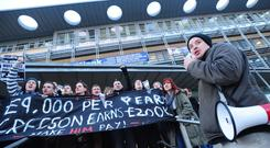 Students unfurl a banner outside the vice-Chancellor's office at Queen's University yesterday during their demonstration against cuts