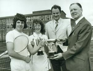 The Northern Bank have presented to Grosvenor High School two perpetual Challenge Cups for tennis. Pictured above, Paul Dunbar receives the Senior Boys from Mr. A. Andrwes, Manager Northern Bank, Castlereagh Road Branch. Also included are Heather Sharpe, winner of the Senior Girls, and Mr. Ken Reid, Headmaster Grosvenor High School, 1973.