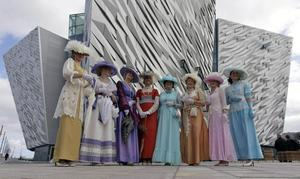 Guests dressed for the occasion arrive for the official opening of  Belfast's impressive new tourist attraction, the 100-million pound ($160 million, euro120 million) Titanic Belfast visitor center, which offers a loving portrait of the excitement, ambition and opulence surrounding the doomed trans-Atlantic liner in Belfast, Northern Ireland, Saturday, March, 31, 2012 (AP Photo/Peter Morrison)