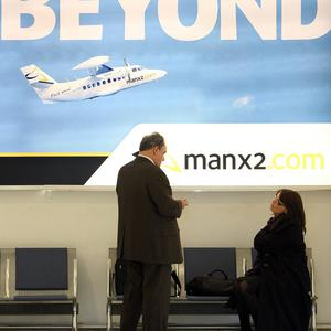Passengers are seen by a Manx 2 poster at George Best Belfast City Airport
