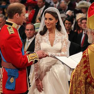 Prince William places a wedding ring on Kate Middleton's finger in front of the Archbishop of Canterbury
