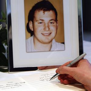 A man signs a book of condolence for Pc Ronan Kerr who died when a booby trap bomb detonated under his car