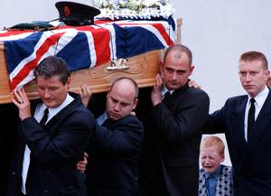 June 1997 Louis Johnston (7), in tears as he follows his dad's coffin from the family church in Lisburn, County Antrim. Constable David Johnston was one of two RUC community officers shot dead by the Provisional IRA in Lurgan, County Armagh just days before the IRA ceasefire was announced. Picture by Alan Lewis