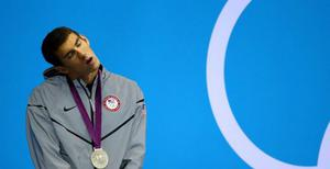 LONDON, ENGLAND - JULY 31:  Silver medallist Michael Phelps of the United States reacts after receiving his medal during the medal ceremony for the Men's 200m Butterfly final on Day 4 of the London 2012 Olympic Games at the Aquatics Centre on July 31, 2012 in London, England.  (Photo by Al Bello/Getty Images)