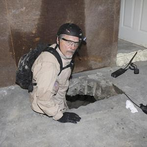 A task force agent lowers himself into a cross-border tunnel that authorities say was used as an underground drug passage (AP)
