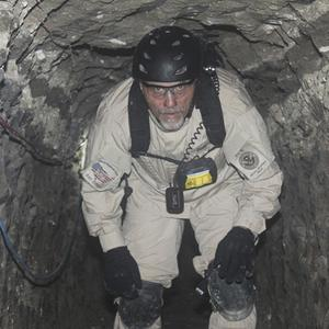 A task force agent crouches inside a cross-border tunnel that authorities say was used as an underground drug passage (AP)