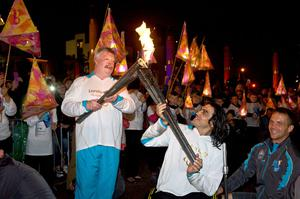 Simon Weston (left) and Nazim Erdem perform a kiss with the Welsh National Flame during the parade to the evening celebration site